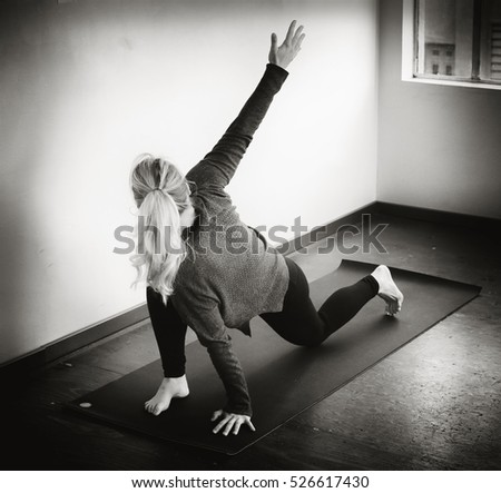 Photo of a very attractive blonde woman doing yoga on her mat. #526617430