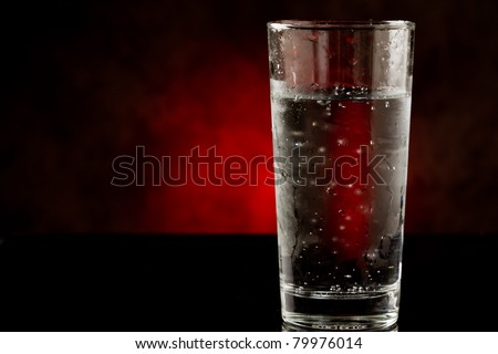 photo of a water glass with sparkling cold water inside on black glass table