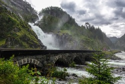 Photo of a waterfall next to a road in Norway.