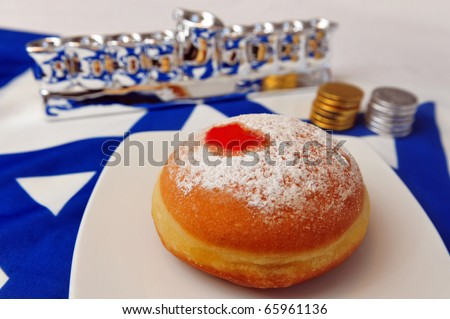 Photo of a white and blue Israeli flag with the star of David with chocolate coins, sufganiya  and silver Menora - objects for the Jewish holiday of Hanukkah.