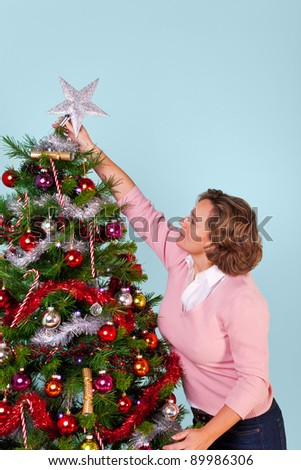 Photo of a woman at home decorating her Christmas tree and finishing off by putting the star on top.