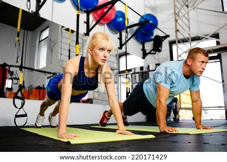 Photo of a woman doing pushups in a gym withe her personal trainer