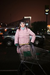 Photo of a woman in the city lights at night with a cart. A model stands right in front of the camera against the backdrop of city life.