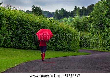 Stock Of A Woman Walking Down Road Holding Red