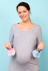 Photo of a woman who is 32 weeks pregnant holding baby booties, pink for a girl and blue for a boy.
