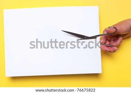 Photo of a womans hand cutting through a blank piece of white paper with chrome scissors on a yellow background, add your own image or text.