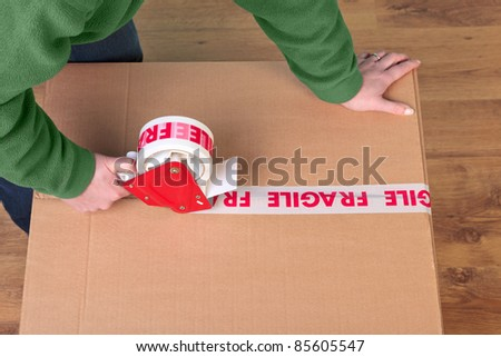 Photo of a womans hands taping up a cardboard box, can be used for removal or logistics related themes.