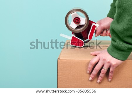 Photo of a womans hands taping up a cardboard box, can be used for removal or logistics related themes. ストックフォト ©