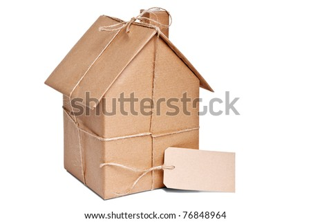Photo of a wrapped house in brown recycled paper with label, cut out on a white background. Stock photo ©
