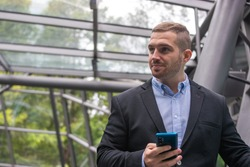 Photo of a young and attractive business man checking his phone. Wearing smart casual clothes. Entrepeneur style