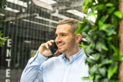 Photo of a young and attractive business man wearing smart casual and elegant clothes talking on the phone while smiling. Smart working. Entrepeneur