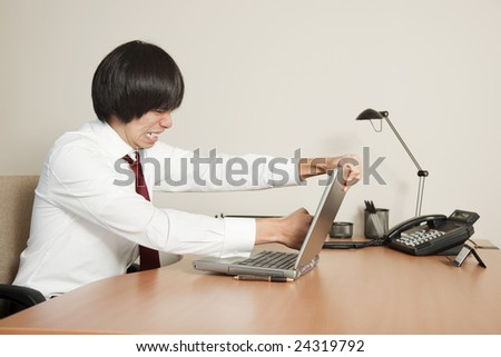 Photo of a young Asian businessman punching his laptop computer screen.