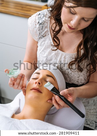 Photo of a young beautiful girl receiving a green facial mask in spa beauty salon.