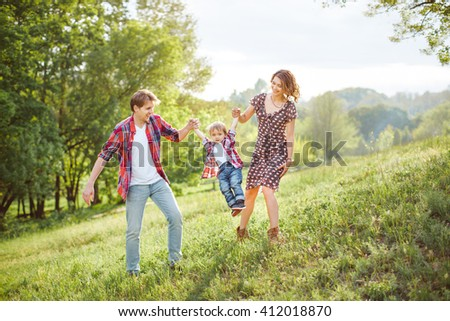 Photo of a young family enjoying holidays in the park on a sunny summer day countryside