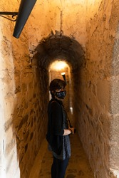 Photo of a young female walking between the small passages illuminated by electric torches inside the ruins of an old medieval castle in Olivenza, Spain