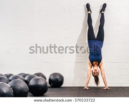 Photo of a young fit woman doing a handstand exercise at a crossfit gym.