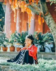 Photo of a young girl in red Hanfu wearing traditional Chinese clothes in a Chinese Buddhist temple in ancient China.