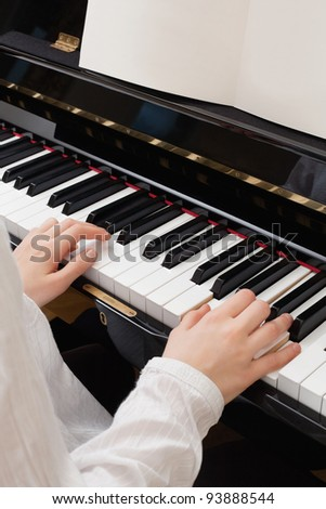 Photo of a young girl playing the piano with sheet music open.