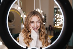 Photo of a young happy cute blonde girl indoors in beauty salon looking at camera through ring light lamp.