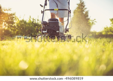 Photo of a young man mowing the grass during the beautiful evening. #496089859