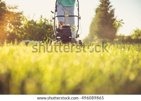 Photo of a young man mowing the grass during the beautiful evening. #496089865