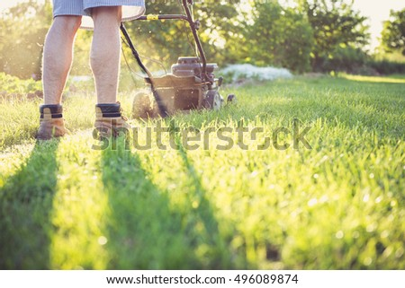 Photo of a young man mowing the grass during the beautiful evening. #496089874