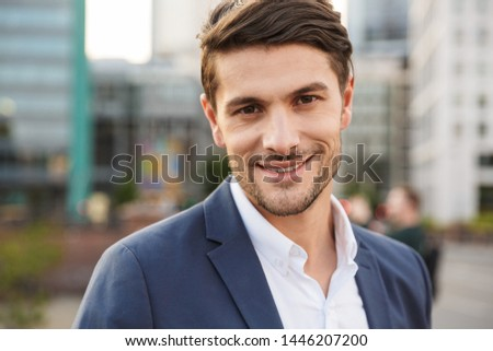 Photo of a young smiling cheery unshaved businessman outdoors on the street looking camera. #1446207200