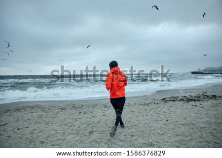 Photo of active sportsman in warm athletic clothes doing physical exercises outdoor, running by seaside before working day, leads healthy sporty lifestyle