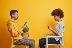 Photo of addicted mixed race woman and man hold mobile phone sit opposite each other on comfortable chairs spends time at home without going out isolated over yellow background use internet.