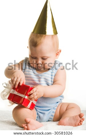 Photo of adorable baby holding birthday present in hands