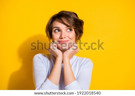 Photo of adorable positive lady look empty space hands cheeks wear white shirt isolated yellow color background