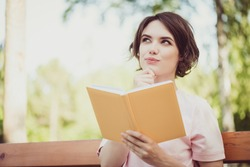 Photo of adorable pretty dreamy young lady look side hand touch chin hold book think imagine story plot get new information facts exam preparing wear pink t-shirt sit bench park outdoors