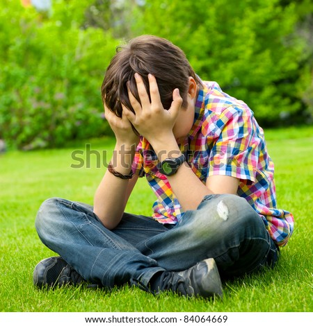 Photo of adorable young boy sitting on the grass at his backyard holding his head and looking down. He is thinking and sad