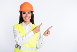 Photo of adviser lady direct fingers empty space toothy smile wear helmet shirt vest isolated white color background