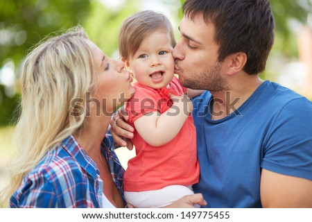 Photo of affectionate parents kissing their small daughter