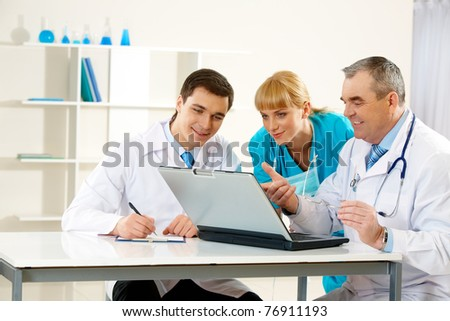 Photo of aged physician pointing at laptop display with two colleagues near by looking at it