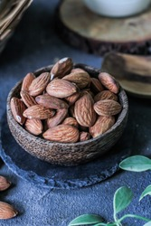 Photo of almond in a wooden bowl. Front View of almond. Almond with wooden spoon or scoop. Raw almond on the table. On rustic board. Images