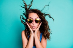 Photo of amazed astonished speechless funky lady model palms face pink specs blast bang hairdo crazy news discount low prices seasonal sale wear blue swimsuit isolated teal color background