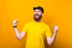 Photo of amazed bearded hipster man in yellow t-shirt celebrating victory or success.
