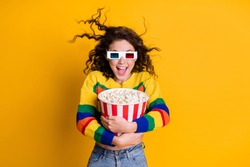 Photo of amazed funky young brunette hair lady hold popcorn watch tv wear spectacles sweater jeans isolated on yellow color background