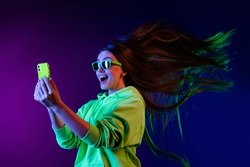 Photo of amazed shocked young woman look phone fast internet fly hair isolated on colorful neon background
