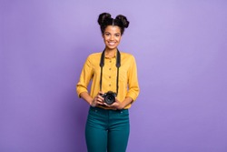 Photo of amazing dark skin lady holding photo digicam in hands positive cheerful mood photographer wear yellow shirt trousers isolated purple color background