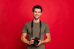 Photo of amazing guy with photo digicam in hands wear casual grey t-shirt isolated on red background