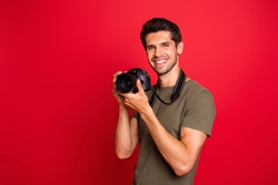 Photo of amazing guy with photo digicam making creative shots wear casual grey t-shirt isolated on red background