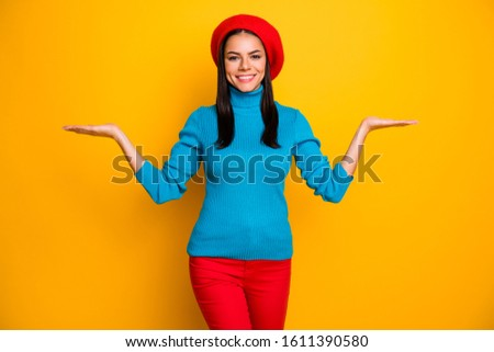 Photo of amazing latin lady beaming smile hold open palms novelty products wear beret hat blue turtleneck sweater red trousers isolated bright yellow color background