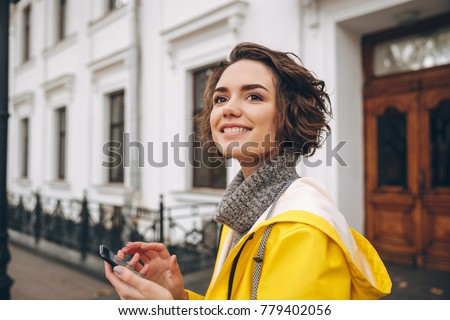 Photo of amazing young woman dressed in raincoat walking outdoors chatting by mobile phone. Looking aside.