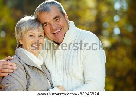 Photo of amorous aged man and woman looking at camera