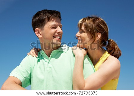Photo of amorous couple smiling at each other while happy woman embracing her husband