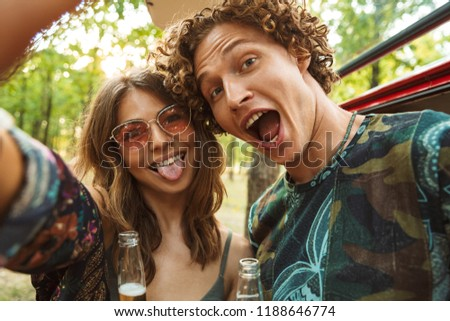 Photo of amusing hippie couple man and woman smiling and taking selfie in forest near retro minivan
