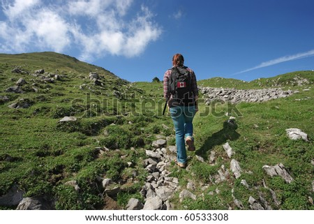 Photo of an active female with backpack hiking up a mountain trail. Slight motion blur on hiker.